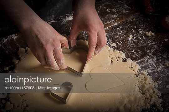 Valentine's Day baking, woman cutting out heart shaped biscuits from dough. - p1100m1157603 by Mint Images