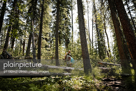 Male surfer carrying surfboards in sunny woods - p1192m2129161 by Hero Images