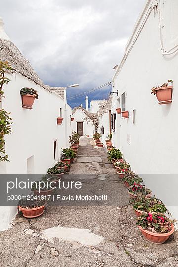 Italy, Apulia, Alberobello, view to alley with rows of flowerpots - p300m2041917 von Flavia Morlachetti