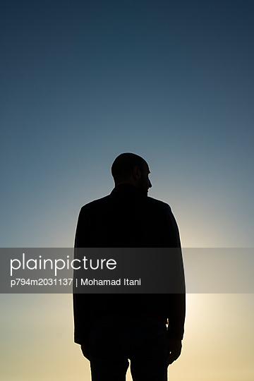 Rückansicht Silhouette eines Mannes der in die Ferne schaut - p794m2031137 von Mohamad Itani