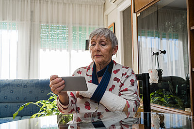 Caucasian white-haired elderly woman with broken arm, sitting at home - p1166m2237056 by Cavan Images