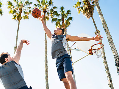 Two young men playing basketball on an outdoor court - p300m1140494 by Lighteffect