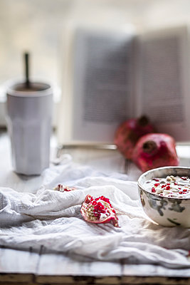 Healthy breakfast with pomegranate in yogurt, coffee and opened book - p300m980422f by Susan Brooks-Dammann