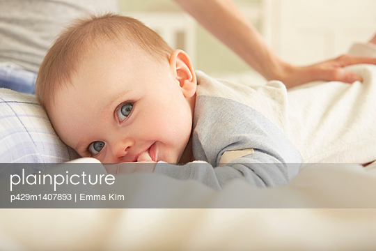 Portrait of baby girl lying on bed with mother - p429m1407893 by Emma Kim