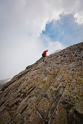 Low angle view of determined hiker climbing rock formations against cloudy sky - p1166m1531498 by Cavan Images