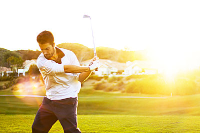 Confident man playing golf at field - p1166m969820f by Cavan Images
