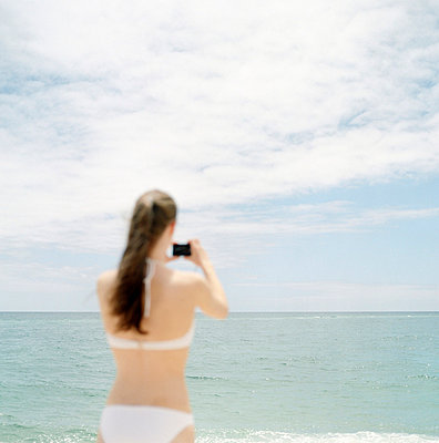 Rear view of a young woman taking a picture with a digital camera on the beach - p3741529 by Karin Smeds