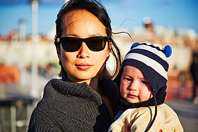 Mother wearing sunglasses holding baby boy - p429m802498 by Cultura