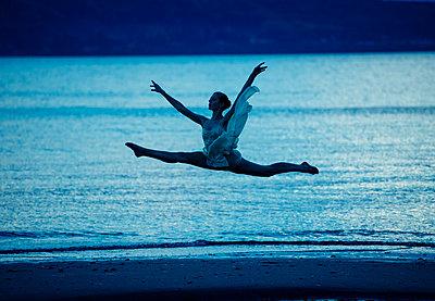 Caucasian ballerina jumping on beach at sunset - p555m1232004 by Pete Saloutos