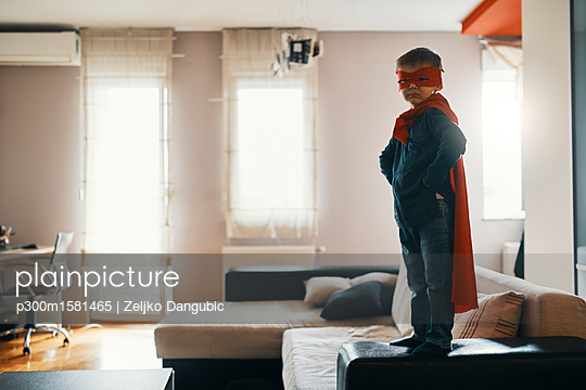 Little boy dressed up as a superhero standing on coffee table at home - p300m1581465 von Zeljko Dangubic