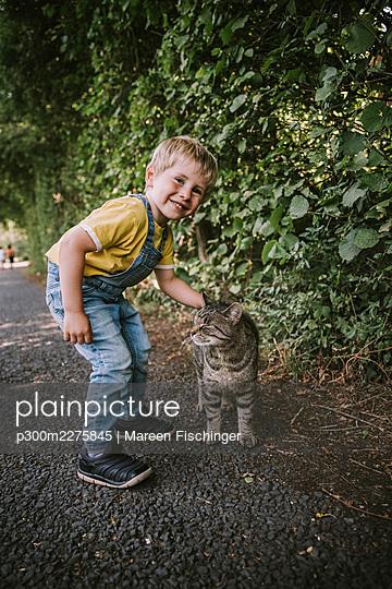 Cute boy stroking stray cat on street - p300m2275845 by Mareen Fischinger