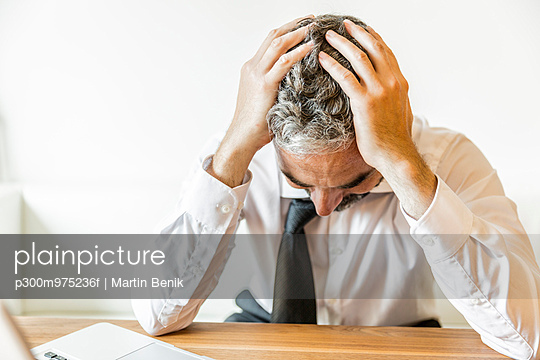 Overstressed businessman with head in his hands - p300m975236f by Martin Benik