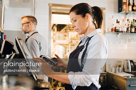 Owner using computer while holding credit card reader in restaurant - p426m2149165 by Maskot