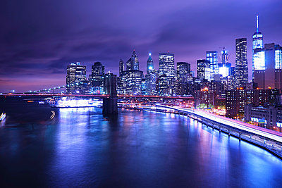 Brooklyn Bridge over river against illuminated city - p1166m1185923 by Cavan Images