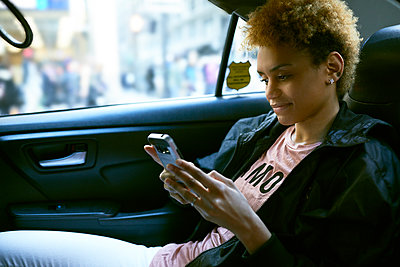 Smiling young woman using phone in taxi - p1166m1474161 by Cavan Images