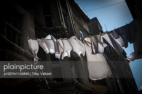 Laundry drying on a string in the street - p1007m1134840 by Tilby Vattard