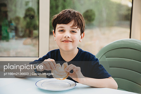 Portrait of boy enjoying cream donut with cream on his cheek - p1166m2136603 by Cavan Images