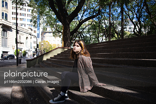 Girl sits on the steps of the city square in Buenos Aires - p1166m2232386 by Cavan Images