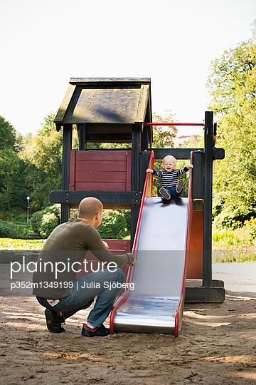 Sweden, Gotaland, Vastra, Dad playing with son (12-17 months) in playground - p352m1349199 by Julia Sjöberg