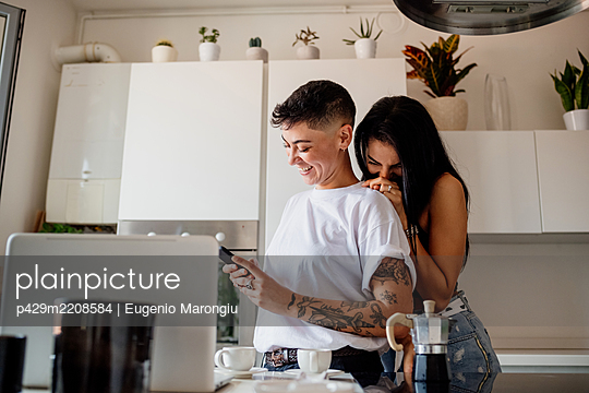 Young lesbian couple standing in kitchen, looking at mobile phone. - p429m2208584 by Eugenio Marongiu