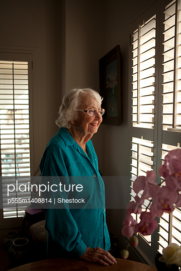 Smiling older Caucasian woman looking out window - p555m1408814 by Shestock