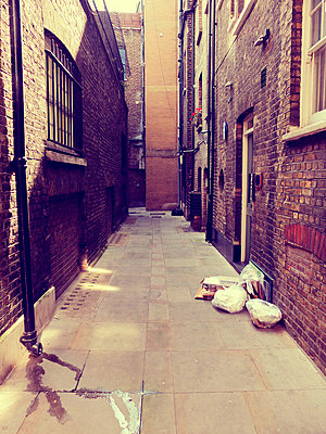 Dirty London alleyway with rubbish sacks - p1072m829228 by Neville Mountford-Hoare