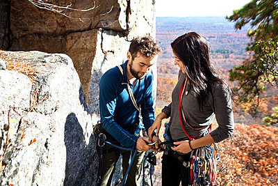 Man assisting girlfriend while rock climbing - p1166m1231440 by Cavan Images