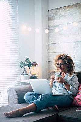 Woman on couch at home with coffee mug and laptop - p300m2103647 by Simona Pilolla