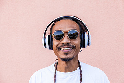 Portrait of mature man with dreadlocks and headphones, listening music - p300m2144793 by Tom Chance