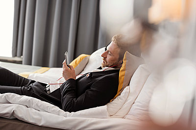 Side view of businessman listening music while lying on bed at hotel room - p426m1442754 by Maskot