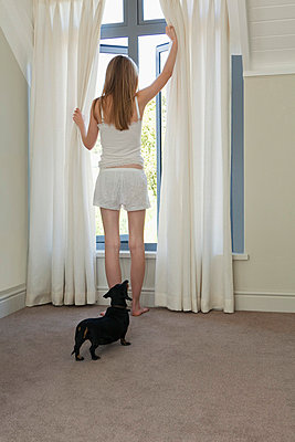 Girl looking out of window - p4296343 by Clarissa Leahy