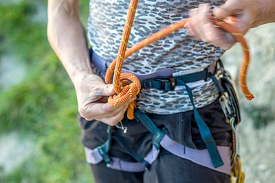 Mid section of woman tying rock onto safety harness - p429m1126035f by Violeta Beral