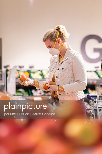 Teenage girl wearing protectice mask and gloves choosing apples at supermarket - p300m2225036 by Anke Scheibe