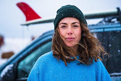 Woman surfer portrait with frozen surfboard - p1166m2177065 by Cavan Images