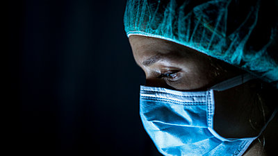 Portrait of young female surgeon, wearing mask and a surgical mask, in front of black background - p1166m2190781 by Cavan Images