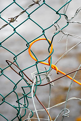 A wire mesh fence repaired with random pieces of other wire - p1302m2081605 by Richard Nixon