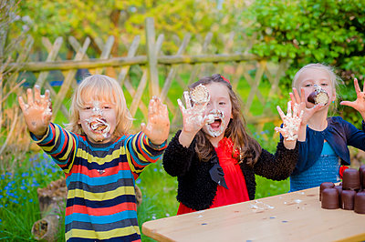 Three children making eating contest with chocolate marshmallows - p300m950456f by Jana Mänz