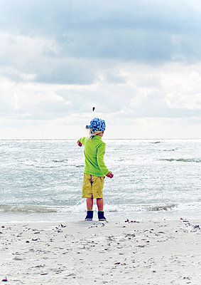Child throwing stones on beach - p312m1493627 by Rebecca Wallin