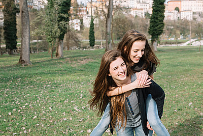 Girlfriends playing piggyback ride in park - p429m2023137 by Alberto Bogo