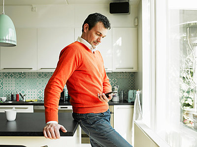 Mature man using cellphone in kitchen - p429m802965f by Soren Hald