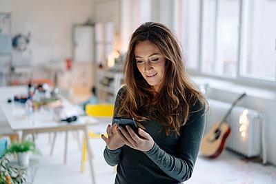 Junge Frau liest SMS auf dem Smartphone - p586m1510382 von Kniel Synnatzschke