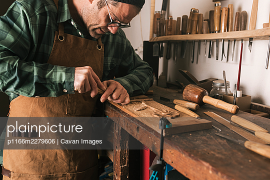 Side shot of a cabinetmaker working on a wood carving with a chisel. - p1166m2279606 by Cavan Images