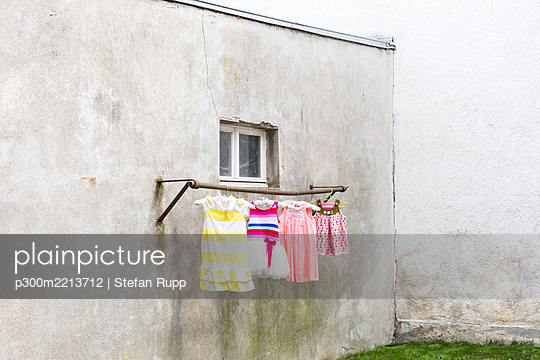 Germany, glum backyard with children's dresses hanging on clothes pole - p300m2213712 by Stefan Rupp