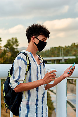 Young afro man with mask is using his mobile on the street - p1166m2201848 by Cavan Images