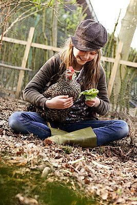 Mädchen füttert Huhn - p1348m1480870 von HANDKE + NEU