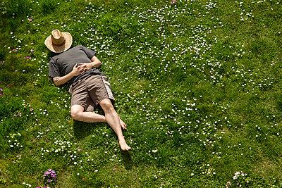 Man lying in grass relaxing - p300m1188599 by Miriam Dörr
