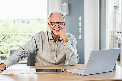 Smiling male professional with hand on chin at desk in home office - p300m2294154 by Uwe Umstätter