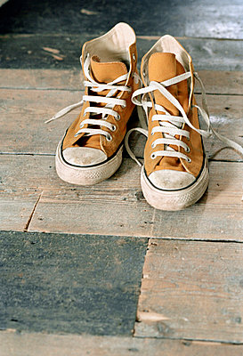 Pair of casual boots on a wooden floor - p349m695133 by Emma Lee
