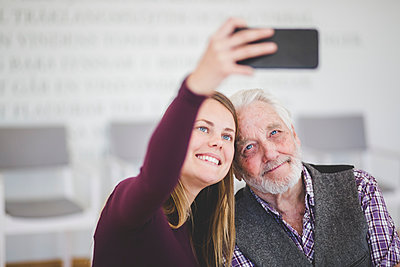 Smiling young woman taking selfie with grandfather while sitting in nursing home - p426m2018563 by Maskot