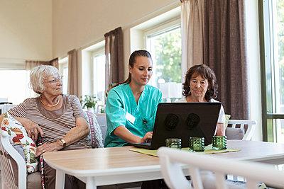 Young nurse using laptop while sitting amidst senior women at nursing home - p426m2072539 by Kentaroo Tryman